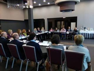Grupa osób siedzi w dużej sali przy stole z dokumentami.