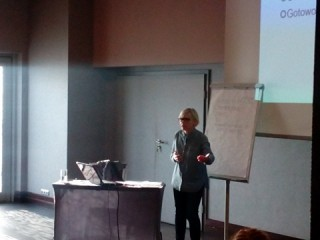 Osoba prowadząca spotkanie przemawia stojąc obok biurka, tablicy oraz wiszącego ekranu projekcyjnego z wyświetloną prezentacją.