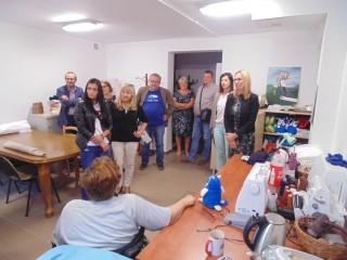 Grupa osób stoi przy wejściu do pracowni w której siedzi kobieta przy stole z maszynami do szycia i pluszowymi zabawkami.