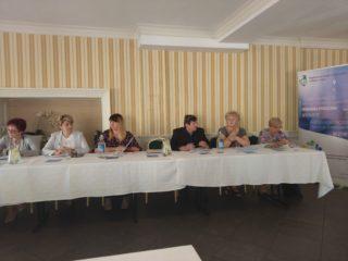 Długi stół z białym obrusem przy którym siedzi grupa osób. Obok stoi baner Ekonomii Społecznej.