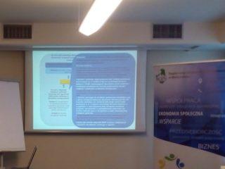 Obraz z projektora przedstawiający niebieskie tabele z tekstem, obok ekranu projektowego stoi jeszcze tablica i baner ekonomii społecznej.