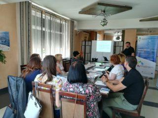 Grupa osób siedzi przy stole z dokumentami i patrzy w stronę prowadzącego który stoi przy ekranie projekcyjnym z wyświetloną prezentacją.