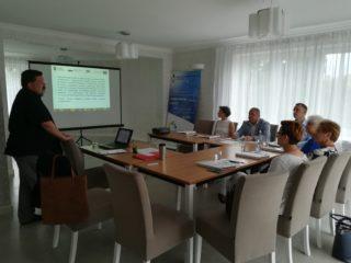 Grupa osób siedzi przy stole i patrzy na prowadzącego który stoi przed laptopem. W tle widać ekran projekcyjny z prezentacją.