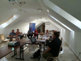 Grupa osób siedzi przy stołach z dokumentami na poddaszu w białych kolorach. Prowadzący siedzi z laptopem i wyświetla prezentacje przy pomocy projektora.