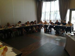 Grupa osób siedzi przy łączonych stołach i przed każdym uczestnikiem leżą dokumenty. Każdy trzyma długopis i cos pisze.