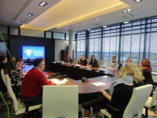 Grupa osób siedzi przy stole w nowoczesnej sali. Na drugim planie widać obraz wyświetlony przez projektor.