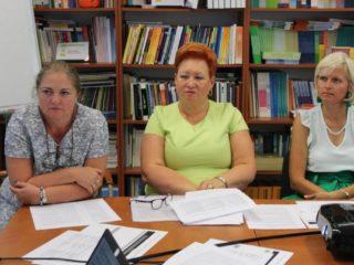 Trzy kobiety siedzą przy stole z dokumentami. Wzrok mają skierowany w jedną stronę. Za ich plecami stoi półka z książkami.