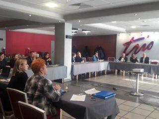 Grupa osób siedzi przy łączonych stołach i patrzy w jednym kierunku. Na środku sali stoi stolik z projektorem.