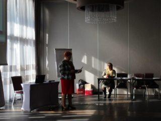 Kobieta z dokumentem w rękach stoi przed biurkiem w centralnej części sali. Obok stoi stół przy którym siedzą dwie osoby.