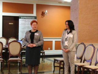 Dwie kobiety stoją obok siebie na pomarańczowej sali ze stołami i krzesłami. Jedna z nich przemawia.