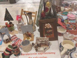 Stoisko z bożonarodzeniowymi ozdobami typu skarpetki, kubki, dzbanki, miniaturowe domki, obrazki itp. Dodatkowo na stole leży kartka z informacją że cenę ustala kupujący.