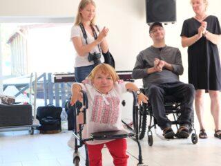 Niska, niepełnosprawna osoba idzie przy pomocy chodzika. Z tyłu widać dwie kobiety i mężczyznę na wózku którzy biją brawo.