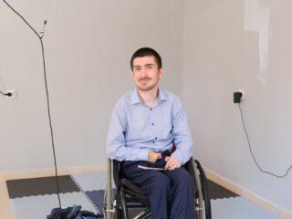 Młody, uśmiechnięty mężczyzna siedzi na wózku inwalidzkim w pustym pomieszczeniu które przechodzi remont.