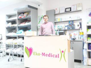 Uśmiechnięty mężczyzna stoi za blatem wewnątrz placówki Eko-Medical która zajmuje się sprzętem medycznym. Wokół na półkach leżą różne artykuły medyczne.