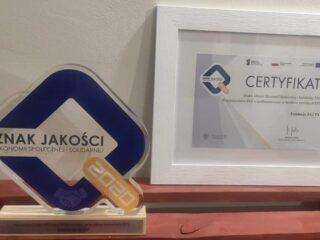 Szklana nagroda Znaku Jakości Ekonomii Społecznej i Solidarnej 2020 oraz Certyfikat oprawiony w ramkę który stoi obok.