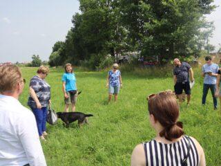 Grupa osób stoi w kółku na zielonej polanie. Miedzy nimi chodzi pies.