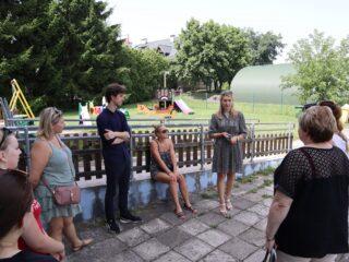 Grupa osób stoi przy płocie na tle placu zabaw i patrzy w stronę kobiety która stoi wśród nich i przemawia.