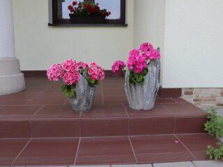 Dwie nietypowe donice z różowymi kwiatami które stoją na stopniu przy budynku.