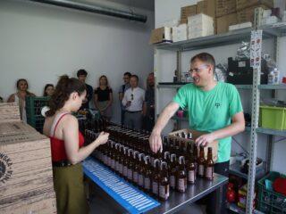 Grupa osób stoi przy ścianie i patrzy w stronę dwóch osób które stoją przy stole z rzędami ciemnych, szklanych butelek.