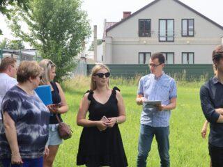 Grupa osób stoi na terenie z wysoką, zieloną trawą. Na drugim planie za płotem widać dom.