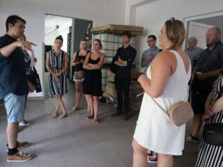 Grupa osób stoi w półokręgu w pomieszczeniu z przejściami do innych pomieszczeń i słucha osoby która stoi przed nimi.