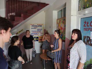 Grupa osób stoi przy drzwiach do żłobka niepublicznego KRECIK. Z tyłu widać schody prowadzące na górę.