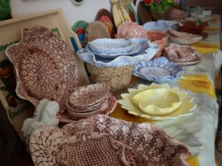 Stół na którym leżą różne nietypowe naczynia typu talerze, misy w różnych wzorach i kolorach.