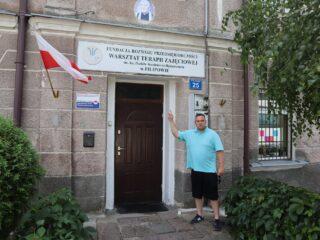 Mężczyzna przy wejściu do budynku Fundacji Rozwoju Przedsiębiorczości - Warsztat Terapii Zajęciowej w Filipowie.