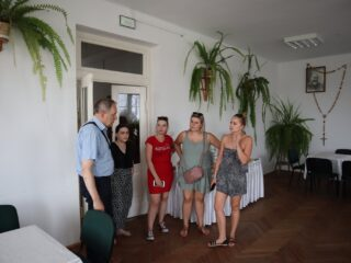 Grupa osób stoi przy drzwiach i rozmawia w jasnym pomieszczeniu z paprotkami. Na jednej ze ścian wiszą obrazy i duży różaniec.