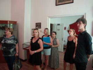Grupa osób stoi przy wejściu w pomieszczeniu ze szklanymi gablotami.