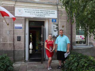 Kobieta i mężczyzna przy wejściu do budynku Fundacji Rozwoju Przedsiębiorczości - Warsztat Terapii Zajęciowej w Filipowie.