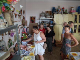 Grupa osób która ogląda wystawę z rękodziełem typu misy, talerze, sztuczne kwiaty, koszyki. W pomieszczeniu stoi duża szafa.
