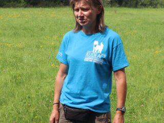 Kobieta w niebieskiej koszulce stoi na zielonej polanie.