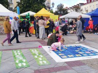 Ogromne gry planszowe rozłożone na Rynku Kościuszki wraz z bawiącymi się dziećmi i rozicami