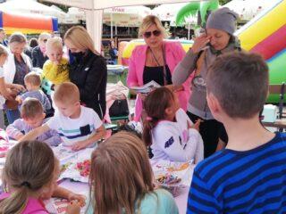 Radosne dzieci bawiący się przy stole zapełnionym kolorowankami i kredkami