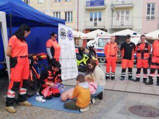Ratownicy medyczni prezętują schemat posępowania pierwszej pomocy w którym czynnie uczestniczą dzieci.