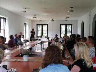 Grupa osób siedzi przy łączonych stołach na sali z białymi ścianami.