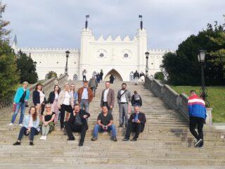 Grupowe zdjęcie na schodach prowadzących do zamku królewskiego w Lublinie. Kilka osób siedzi na schodach.