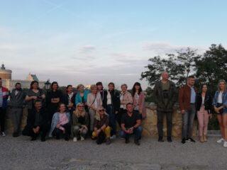 Grupowe zdjęcie przy murku. W tle widać zamek królewski w Lublinie.