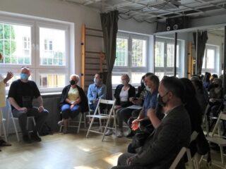 Grupa osób siedzi na składanych krzesłach w półokręgu na jasnej sali z drabinkami przy ścianie i słucha kobiety w białym stroju.