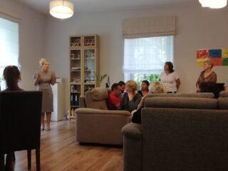 Grupa osób w jasnym pokoju wyposażonym w dwie kapany, szafki i stół z krzesłami. Większość patrzy w stronę mówiącej kobiety.
