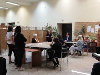 Duża sala rozdzielona parawanem. Na widocznej części grupa osób siedzi przy łączonych stołach i słucha mówiącej kobiety.
