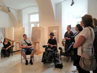Grupa osób oraz mężczyzna na elektrycznym wózku inwalidzkim. Z tyłu na sztalugach stoją obrazy.