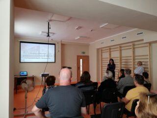 Sala z drabinkami przy ścianie. Na sali siedzi grupa osób w kilku rzędach i ogląda prezentację multimedialną.