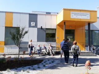Nowoczesny żółto-szary budynek. Przed wejściem siedzi grupa osób na ławce oraz kilka osób wchodzi do budynku.