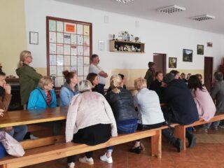 Grupa osób siedzi w sali na ławkach przy stole i patrzy w kierunku mężczyzny w czerwonym stroju i czapce z futra.