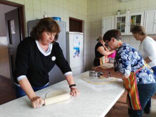 Cztery kobiety robią ciasto w kuchni. Jedna z nich wałkuje ciasto.