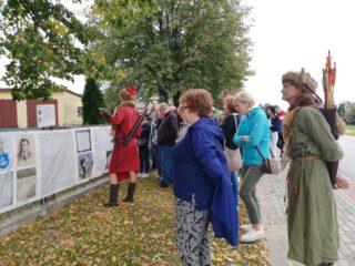 Grupa osób wraz z dwoma przewodnikami w historycznych strojach z futrem i łukami stoi przed płotem z zdjęciami i tekstem historycznym.