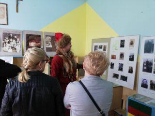 Mężczyzna w czerwonym stroju i futrze z lisa oprowadza ludzi po sali z historycznymi zdjęciami.